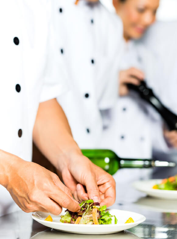 Penfield Olives food service olives and oils page image, chef plating a salad drizzled in olive oil.