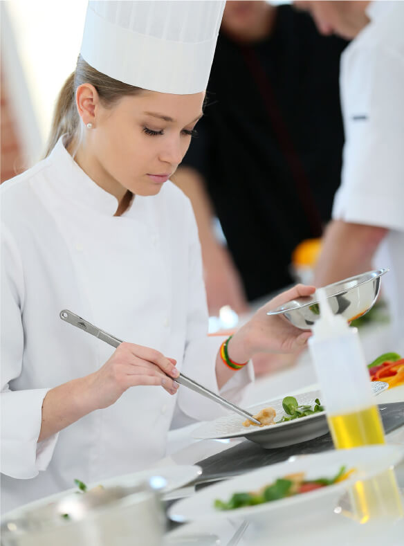 Penfield Olives food service page image of a young female chef cooking with extra virgin olive oil.