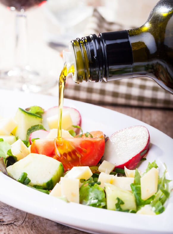 Penfield Olives retail page image of extra virgin olive oil being drizzled over a salad.