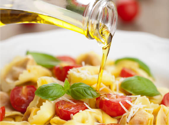 Penfield Olives retail olives products South Australia page pic, drizzling extra virgin olive oil over a pasta salad.