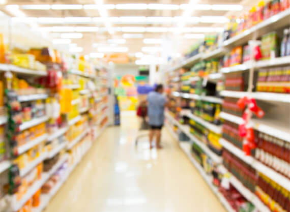 Penfield Olives olive producers slider pic, blurred image of woman shopping in a supermarket isle.
